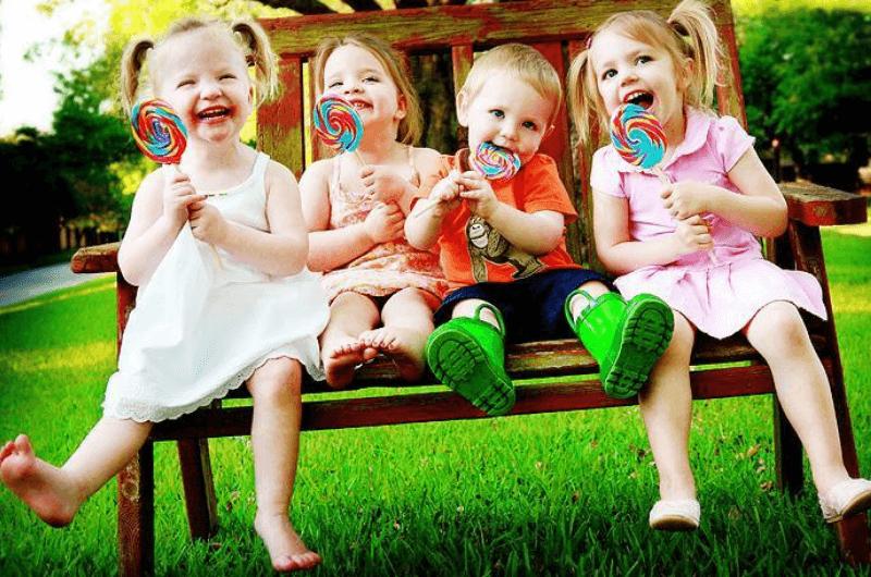 Kids sitting on the bench, eating lollipops.